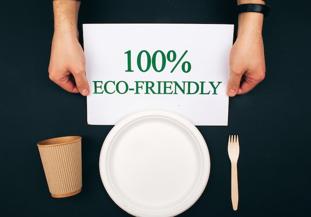 Pollution prevention. paper with word eco-friendly near wooden paper plate, cup and fork on dark background, top view. time to change. new rules to reduce plastic waste, eu directive.