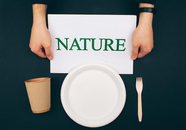 오염 예방. 나무 종이 접시, 컵 및 어두운 배경, 평면도에 포크 근처 단어 자연 종이. 변경할 시간. 플라스틱 폐기물을 줄이기위한 새로운 규칙, eu 지침. 재사용 재활용 감소