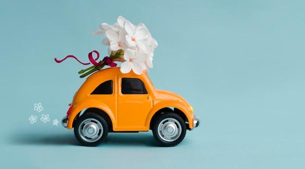 ポルタヴァウクライナ2021年5月20日オレンジ色のレトロな車が花を届けるおもちゃの車は青い背景にギフト用の白いライラックの花の花束を運ぶ