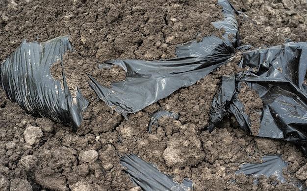 바닥에 폴리에틸렌 백. 비닐 봉투. 활. 환경 오염, 땅 속 쓰레기 투기 지구의 생태 문제
