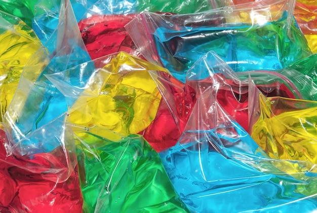 色とりどりの液体で満たされたポリエチレンの小さなバッグ抽象的な背景とテクスチャ