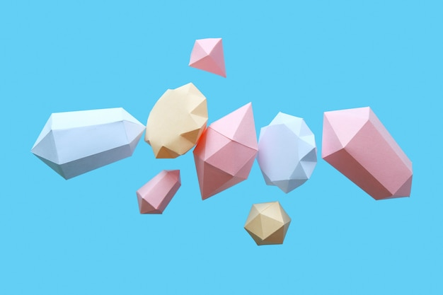Polygonal diamonds made of paper on a blue