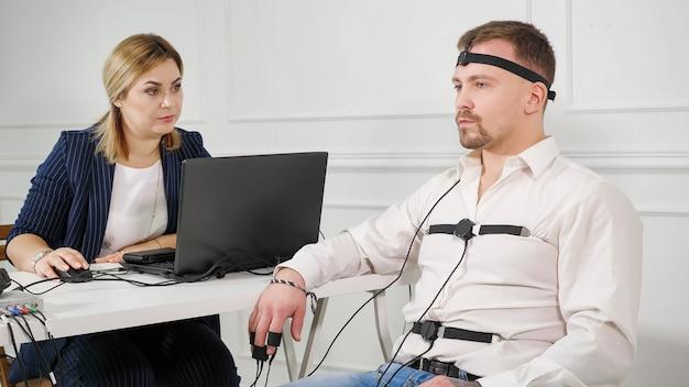 Техник-полиграф читает вопросы с ноутбука. человек подключен к цепи детектора лжи.