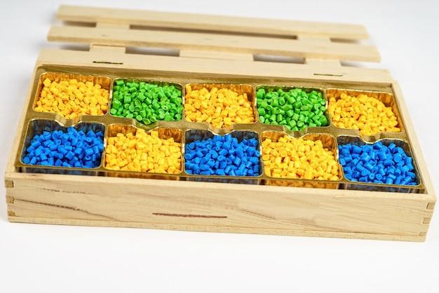 Пластиковые гранулы полимерного красителя в деревянном ящике