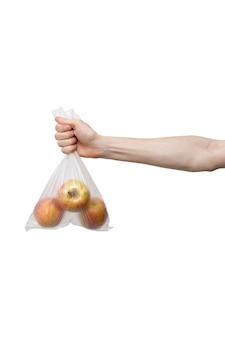 白で隔離される手で開催されたポリエチレンバッグ。新鮮なリンゴのパケットを保持している男