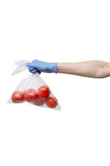 Полиэтиленовый пакет с помидорами, держа в руке синие перчатки на белой стене