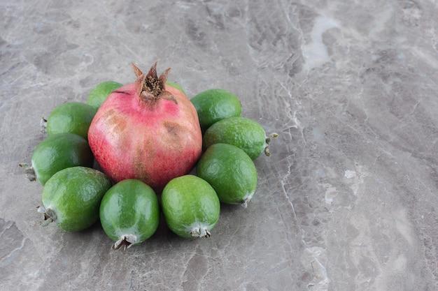 Pomegranante inanellato con feijoas su superficie di marmo