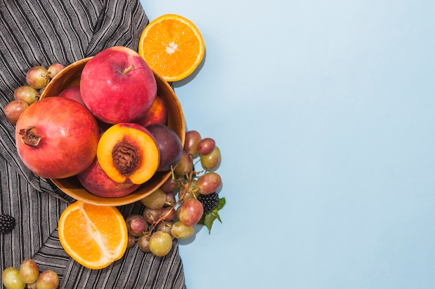 Pomegranate; apple; peach; grapes and halved citrus fruits on blue background