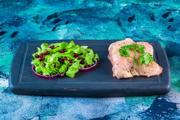 Гранатовые ядра, листья салата с луковым кольцом рядом с куриной грудкой на деревянном подносе