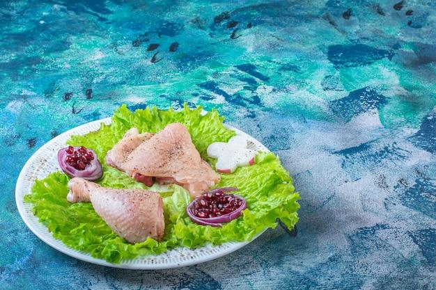 Гранатовые ядра, листья салата с луковым кольцом рядом с куриным мясом на тарелке