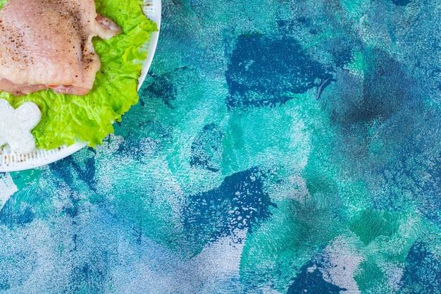 ザクロの仮種皮、プレート上の鶏肉の横にオニオンリングが付いたレタスの葉