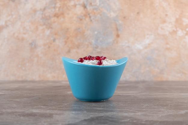Гранатовые зерна на каше в тарелке, на мраморной поверхности