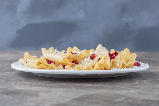 Arilli di melograno con sfoglie di lasagne sul piatto, sul piano di marmo.