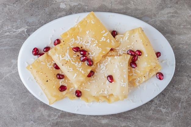 Arilli di melograno con sfoglie di lasagne sul piatto, sul marmo.