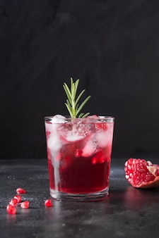 Pomegranate christmas cocktail with rosemary, champagne, club soda on black. close up.