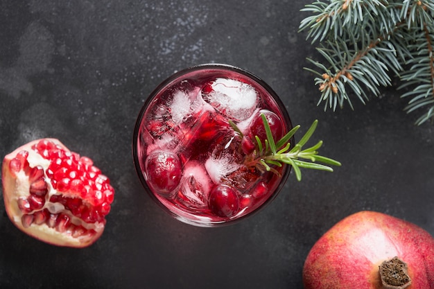 Pomegranate christmas cocktail with rosemary, champagne, club soda on black. view from above.