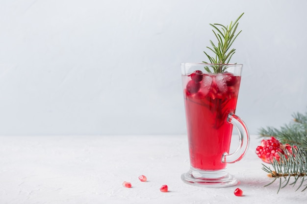 Pomegranate christmas cocktail with rosemary, champagne, club soda on grey concrete table.