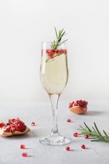 Гранатовый рождественский коктейль с розмарином, шампанским, клубной содой на сером столе. рождественский праздничный напиток.