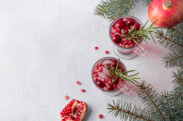 Гранатовый рождественский коктейль с розмарином, клюквой, шампанским, клубной содой на сером бетонном столе. рождественский напиток.