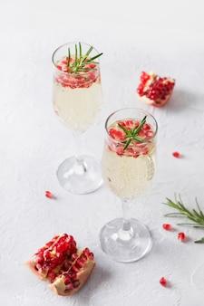 ザクロクリスマスカクテルローズマリー、白いテーブルにスパークリングワイン。クリスマスホリデードリンク。