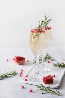 ザクロクリスマスカクテルローズマリー、白いテーブルにスパークリングワイン。