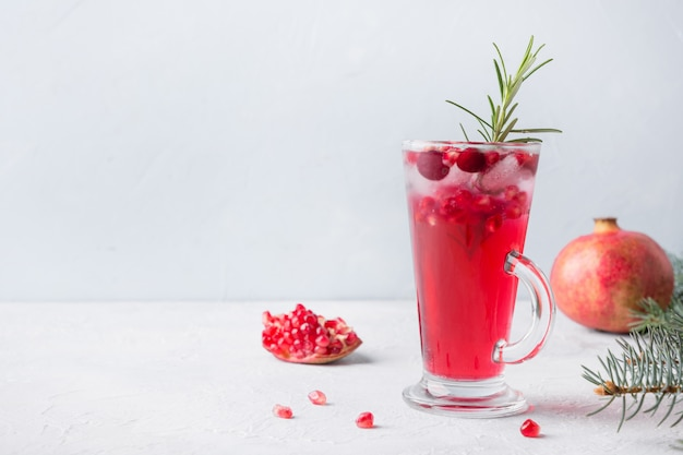 Pomegranate cocktail with rosemary, champagne, club soda on grey concrete table.