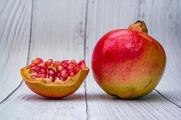 Pomegranate fresh fruit on wood white .