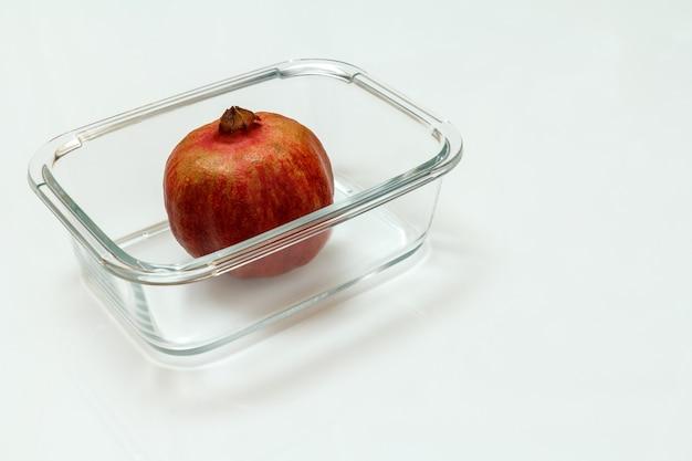 白い背景の上のガラスのボウルにザクロの果実。有機フルーツ。