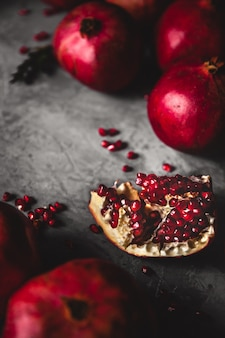 Pomegranate fruit. ripe and juicy pomegranate on rustic grey wall with copy space for your text.