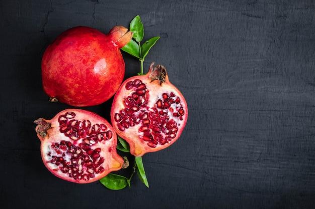 Pomegranate fruit sliced on a black background