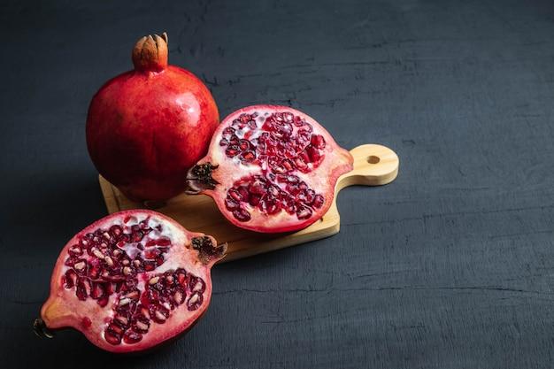 Pomegranate fruit sliced on a black