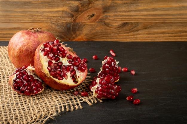 素朴な背景にジューシーな種子とザクロの果実