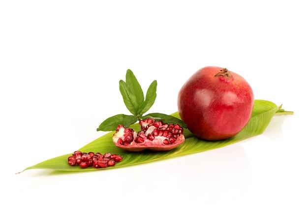 白い背景で隔離のザクロの果実と種子。