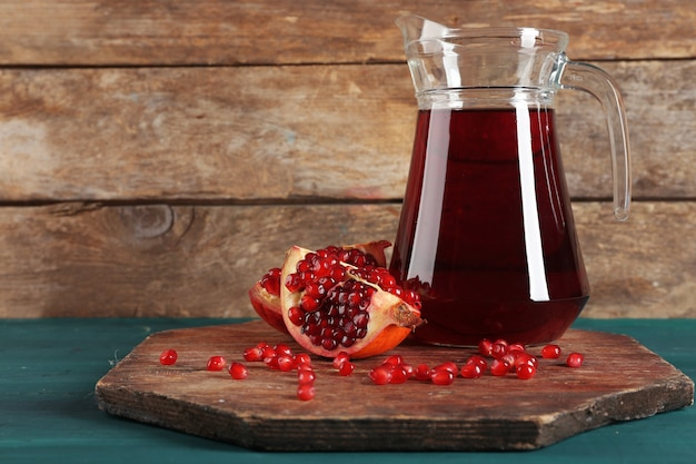 Pomegranate and glass jug of fresh juice on wooden table