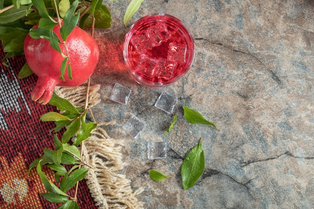 Pomegranate and glass of juice on stone background with leaves