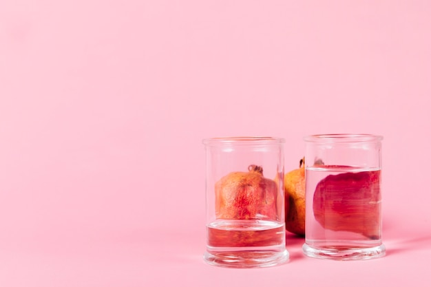 Pomegranate behind glasses with water