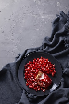 Pomegranate grains on a plate on a dark gray background with drapery