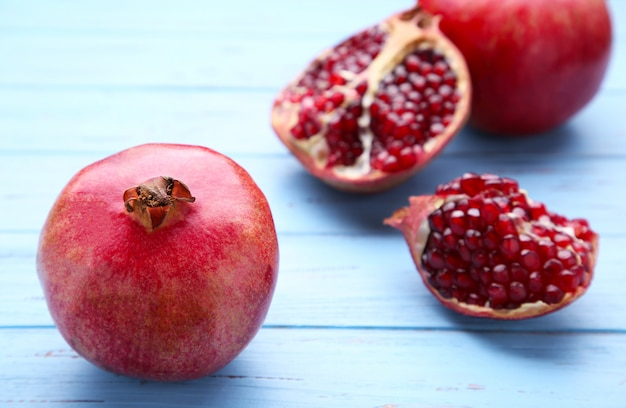 Pomegranate and half of ripe pomegranate on a blue background