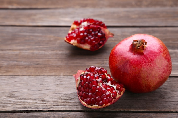 Pomegranate and half of ripe pomegranate on a grey background