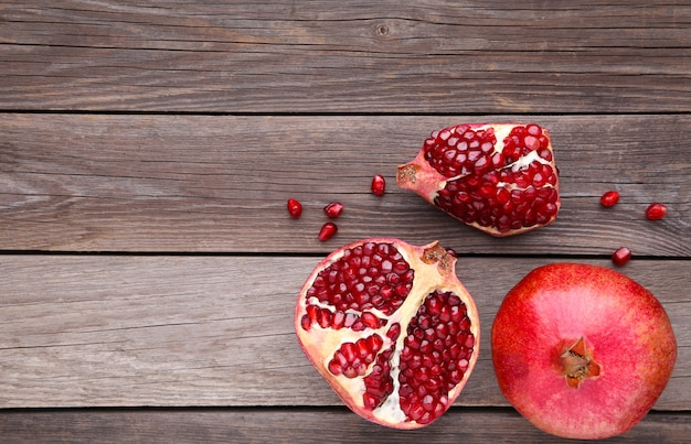Pomegranate and half of ripe pomegranate on a grey wooden background
