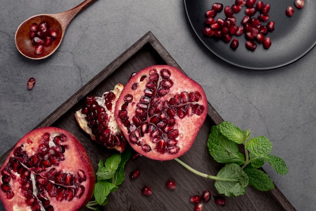 Pomegranate halfs on tray with mint
