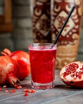 Pomegranate juice in glass with pipe