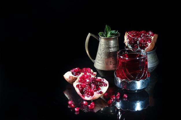 Гранатовый сок в стакане и дольки граната на темной поверхности. . натюрморт.