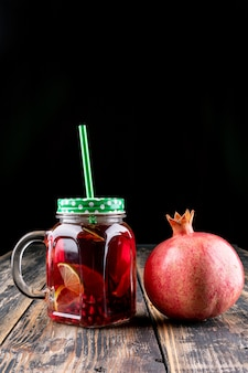 Pomegranate juice in jar on wooden table
