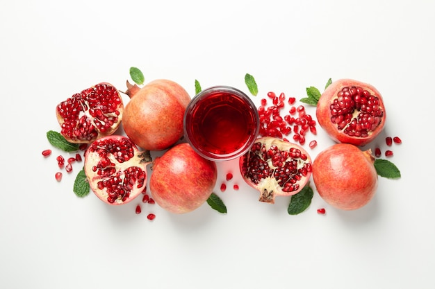 Pomegranate, juice and seeds on white, top view