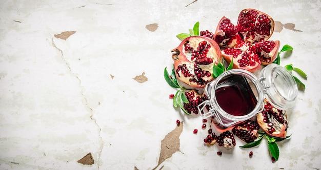 Гранатовый сок с кусочками граната и листьями. на деревенском фоне. свободное место для текста. вид сверху