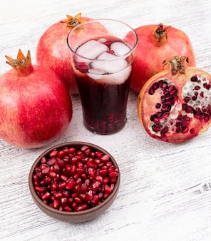 Pomegranate juice with ice cubes and pomegranate on white wooden table