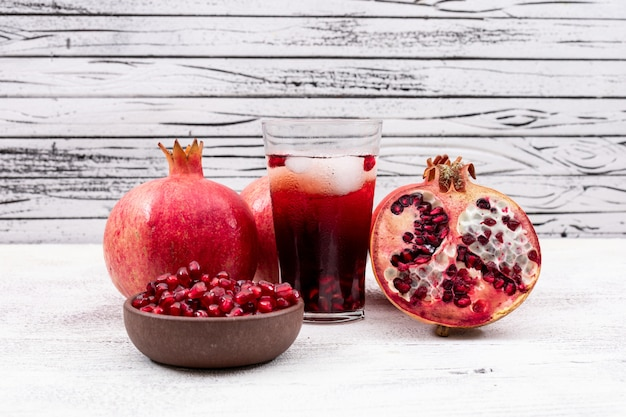 Pomegranate juice with pomegranate on white table