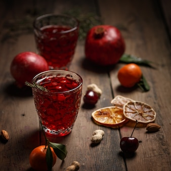 Pomegranate juice with pomegranates and dried fruits on a wooden table. country style.