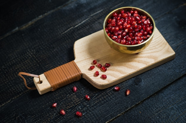 Pomegranate kernels in a bowl on a wooden cutting board.